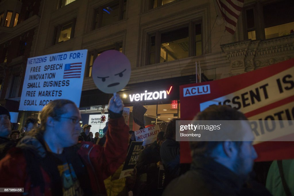 Demonstrators hold up signs during a net neutrality protest outside a Verizon Communications Inc. store in Boston, Massachusetts, U.S., on Thursday, Dec. 7, 2017. The debate over internet regulation has steadily morphed over the last few years from an insular fight between telecom experts into a standard-issue political screaming match. Photographer: Scott Eisen/Bloomberg via Getty Images