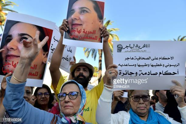Demonstrators hold up signs during a protest calling to free Hajar Raissouni a Moroccan journalist who was sentenced to one year in jail for an...