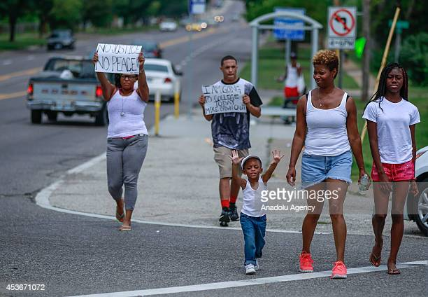 Demonstrators hold up signs during a rally to protest the shooting death of an unarmed teen by a police officer nearly a week ago in the St Louis...