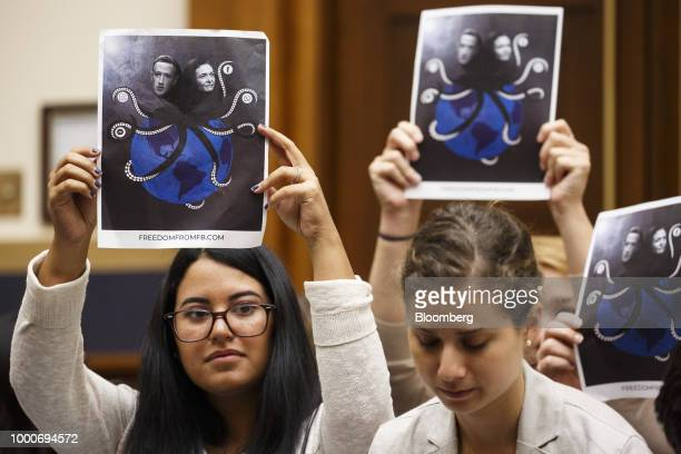 Demonstrators hold up signs protesting Facebook during a House Judiciary Committee on social media filtering practices in Washington DC US on Tuesday...