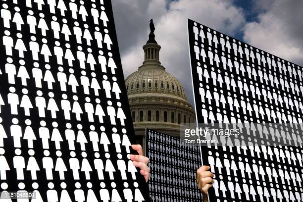 Demonstrators hold up signs representing the 11,400 victims of gun violence discussed by congressional members during a press conference with...