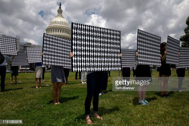 Demonstrators hold up signs representing the 11400 victims of gun violence discussed by congressional members during a press conference with...