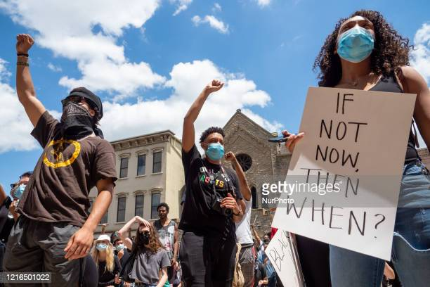 Demonstrators hold up their hands and signs during a Mass Action for Black Liberation protest and march from Washington Park to City Hall following...