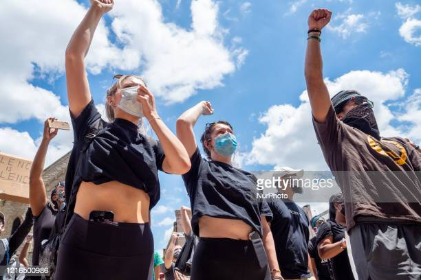 Demonstrators hold up their hands during a Mass Action for Black Liberation protest and march from Washington Park to City Hall following the alleged...