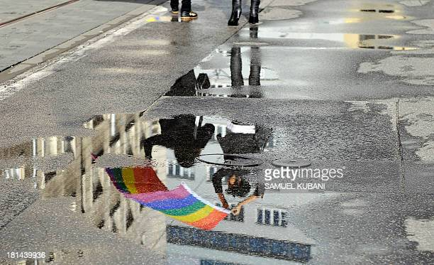 Demonstrators holding a rainbow flag are reflected in a rain puddle during the Rainbow Pride Parade a march for the human rights of nonheterosexual...