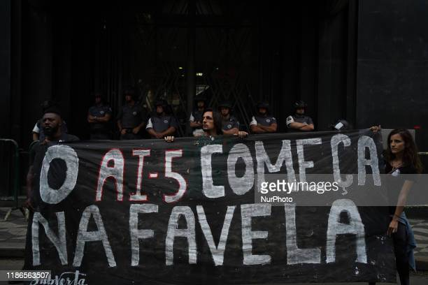 """Demonstrators holding a sign that reads """"AI-5 begins in favela"""" which mentions Institutional Act number of 1968 during a protest about the..."""