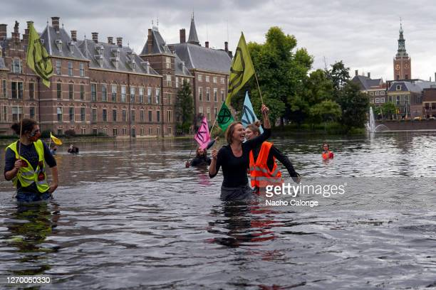 Demonstrators holding flags get into Lake Hofvijver next to the parliament in protest during the demonstration in The Hague on September 1 2020 in...