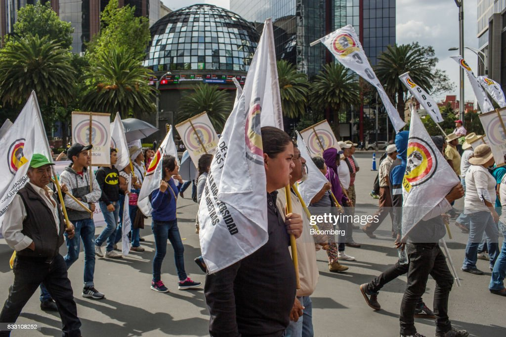 Demonstrators holding flags walk past the Mexican Stock Exchange during a protest against the North American Free Trade Agreement (NAFTA) in Mexico City, Mexico, on Wednesday, Aug. 16, 2017. U.S. Trade Representative Robert Lighthizer made clear Wednesday, on the first day of Nafta renegotiation talks with Mexico and Canada, that the administration will push to win back the jobs and manufacturing capacity the U.S. lost under Nafta. Photographer: Brett Gundlock/ Bloomberg