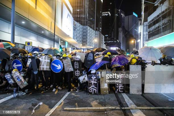 Demonstrators holding shields reading Freedom, from left, Revolution and Hong Kong in Chinese stand off against riot police on Des Voeux Road West...