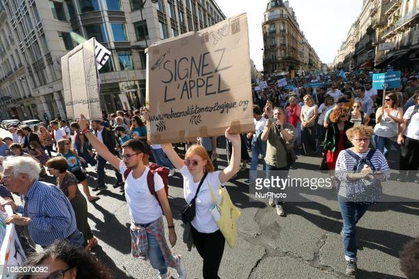 Demonstrators holding signs and banners take part in a march against climate change in front of the Paris Opera on October 13 2018