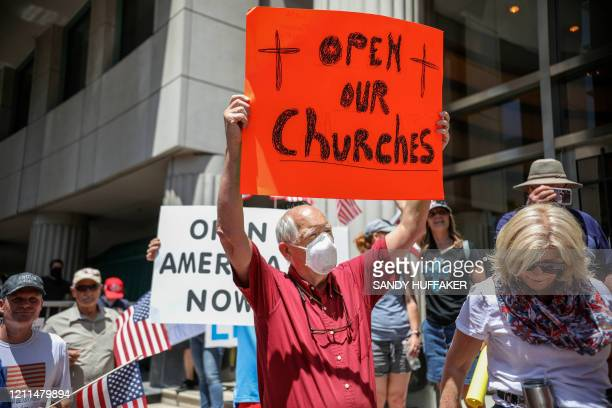 Demonstrators holding signs demanding their church to reopen, protest during a rally to re-open California and against Stay-At-Home directives on May...