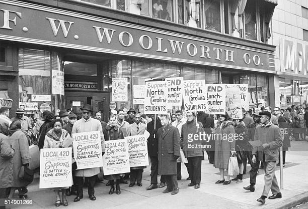 Demonstrators holding signs protest in front of an F.W. Woolworth store in Harlem to oppose lunch counter discrimination practiced in Woolworth...