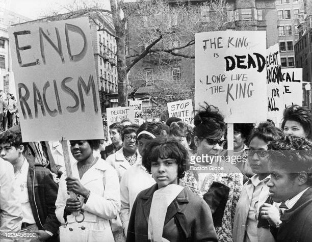 """Demonstrators holding signs reading """"end racism"""" and """"The King is Dead, Long Live The King"""" gather on the Boston Common opposite the Massachusetts..."""