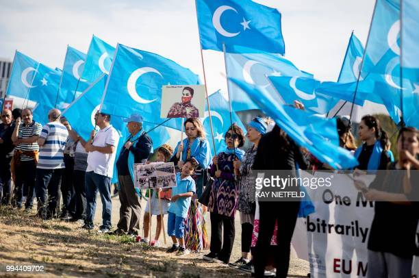 Demonstrators holding Uighur flags demonstrate next to the Chancellery in Berlin on July 9 prior a meeting between German Chancellor and Chinese...