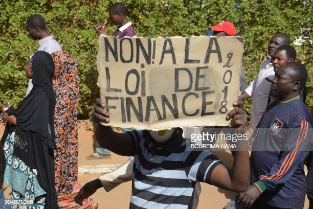 Demonstrators holds a banner as they take part in a march in Niamey on January 14 2018 to protest against the Niger's 2018 budget law / AFP PHOTO /...