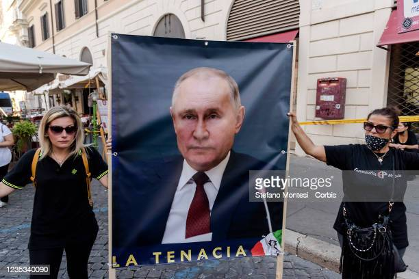 Demonstrators holds a banner with a portrait President of Russia, Vladimir Putin during a demonstration in center city, organized by the far right...
