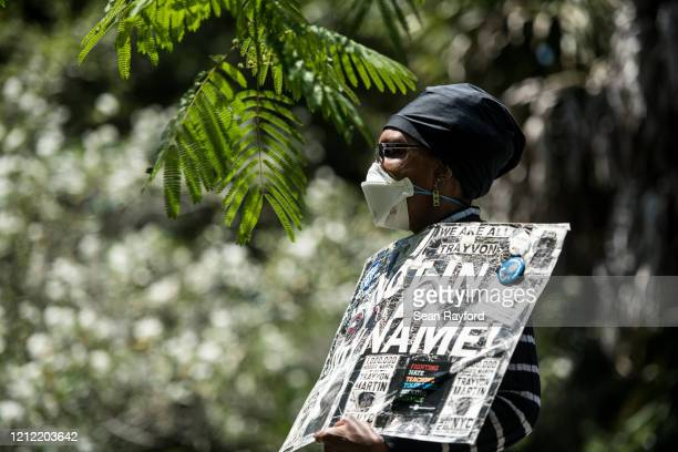 Demonstrators holds a sign for Ahmaud Arbery near where he was shot and killed May 8, 2020 in Brunswick, Georgia. Gregory McMichael and Travis...