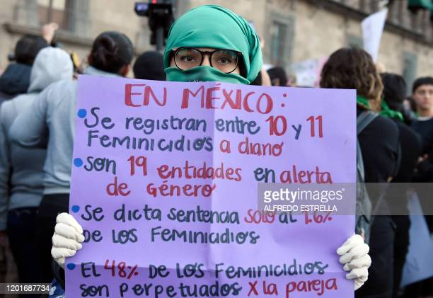 Demonstrators holds a sign reportedly showing femicide statistics in Mexico as women gather outside the National Palace, in Mexico City, on February...