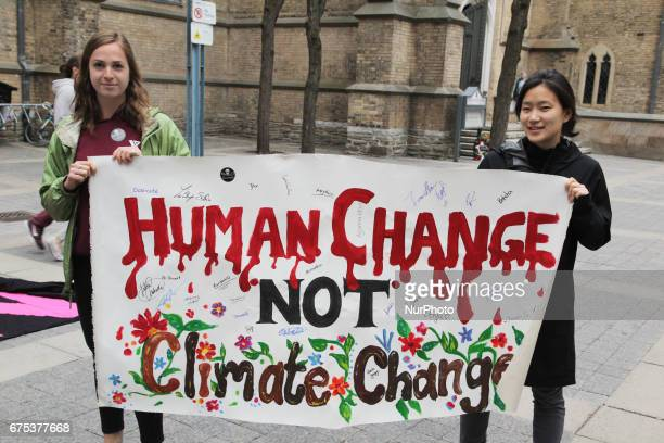 Demonstrators holds a sign saying 'human change not climate change' as hundreds of Canadians took part in a massive march against climate change...