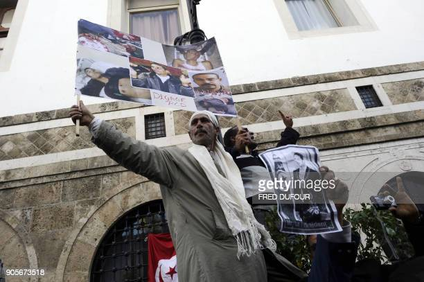 A demonstrators holds up a poster of atrocities which reads 'Get out RCD ' as others gesture and shout slogans during a demonstration on January 21...