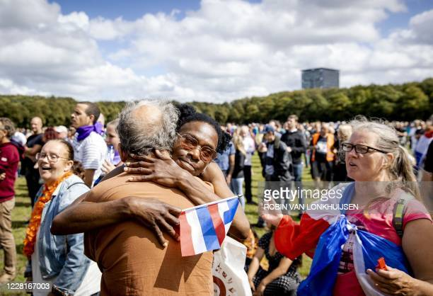 Demonstrators hug as they gather to protest against coronavirus restrictions measures on the Malieveld, in The Hague, The Netherlands, on August 23,...