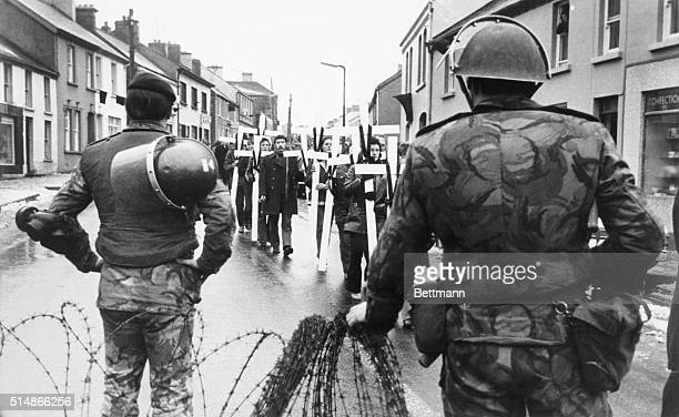 Demonstrators in Dungiven Northern Ireland march past British troops on February 6 to lay crosses on the steps of the local Royal Ulster Constabulary...