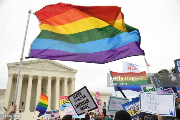 Demonstrators in favor of LGBT rights rally outside the US Supreme Court in Washington, DC, October 8 as the Court holds oral arguments in three...