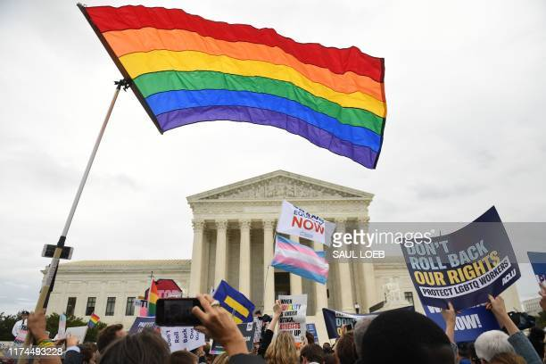 Demonstrators in favour of LGBT rights rally outside the US Supreme Court in Washington DC October 8 as the Court holds oral arguments in three cases...