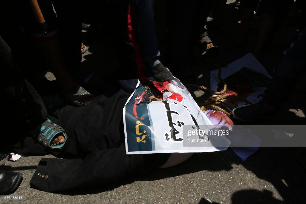 Demonstrators in Gaza against President Mahmoud Abbas burn a picture during mass demonstrations in the Gaza Strip on 2 May 2017