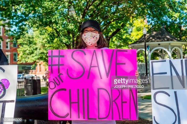 """Demonstrators in Keene, New Hampshire, gather at a """"Save the Children Rally"""" to protest child sex trafficking and pedophilia around the world, on..."""