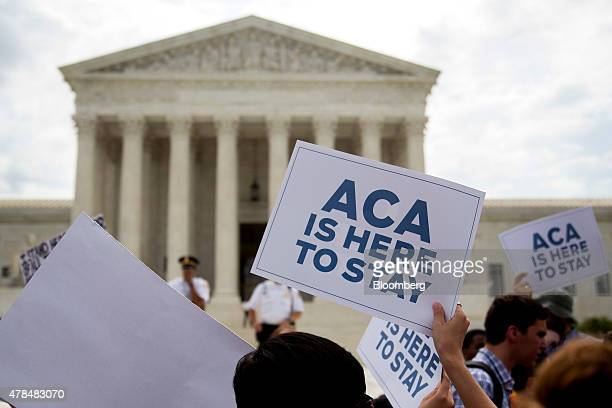 Demonstrators in support of US President Barack Obama's healthcare law the Affordable Care Act hold up 'ACA is Here to Stay' signs after the US...