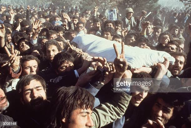Demonstrators in Teheran lifting a shrouded body over the heads of the crowd during the Iranian Revolution