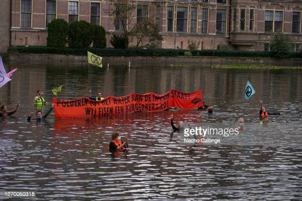 Demonstrators in the lake Hofvijver chant and hold a banner on September 1 2020 in The Hague Netherlands Coinciding with the start of the new...