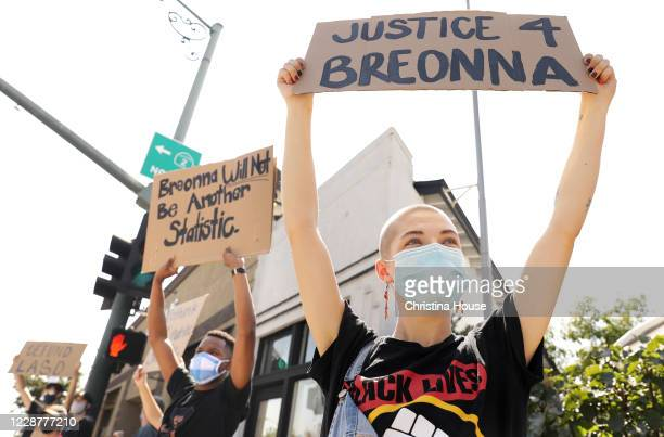 Demonstrators including Ell M of La Cañada right and Justin Warren of Simi Valley at left hold signs at the intersection of Foothill Boulevard and...
