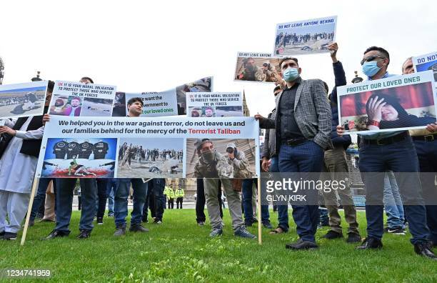 Demonstrators, including former interpreters for the British Army in Afghanistan, hold placards as they protest opposite the Houses of Parliament in...