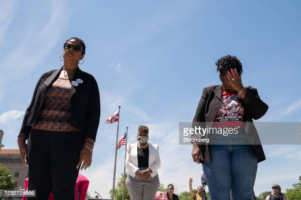 """Demonstrators, including Gwen Carr, mother of Eric Garner, center, pray during a """"Hear the Cry"""" rally at Freedom Plaza in Washington, D.C., U.S., on..."""