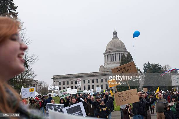 Demonstrators including Julia Cox shout to passing cars in front of the capitol building during a progun rally on January 19 2013 in Olympia...