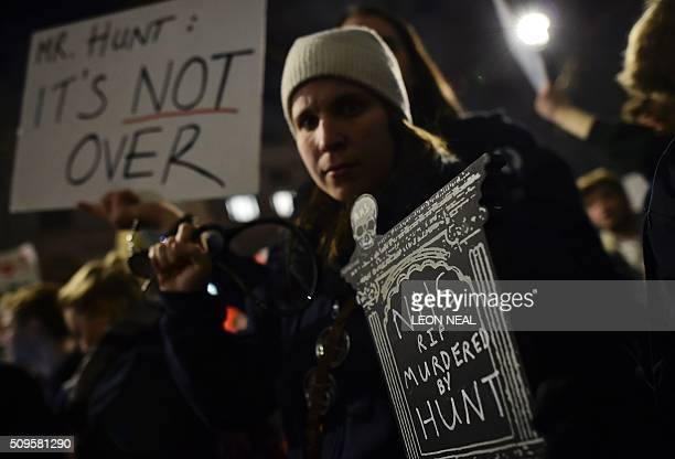 Demonstrators including junior doctors gather with placards outside the Department of Health on Whitehall in central London on February 11 to protest...