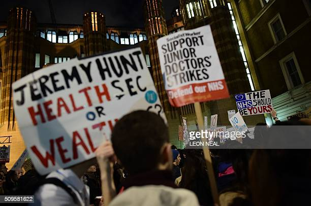 Demonstrators including junior doctors hold placards as they gather outside the Department of Health on Whitehall in central London on February 11 to...