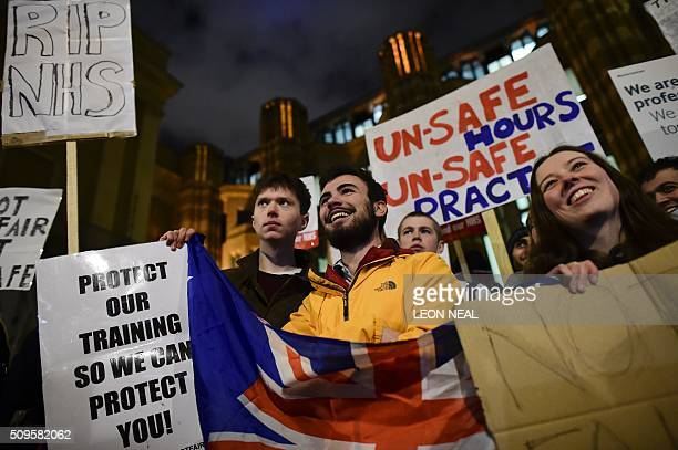 Demonstrators including Junior doctors hold placards outside the Department of Health on Whitehall in central London on February 11 to protest...