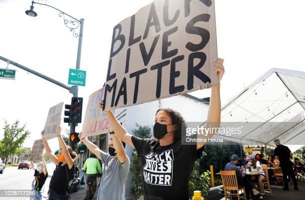 Demonstrators including Kamden Gray of La Cañada center and Michael Khatchadourian of Pasadena at left hold signs at the intersection of Foothill...