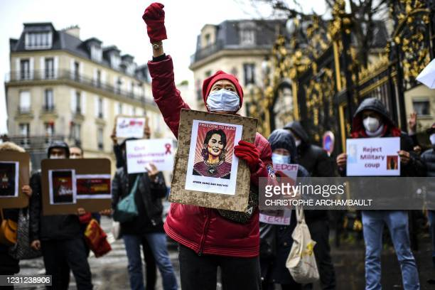 Demonstrators including Myanmar nationals, hold placards and shout slogans during a protest against the military coup and to demand the release of...