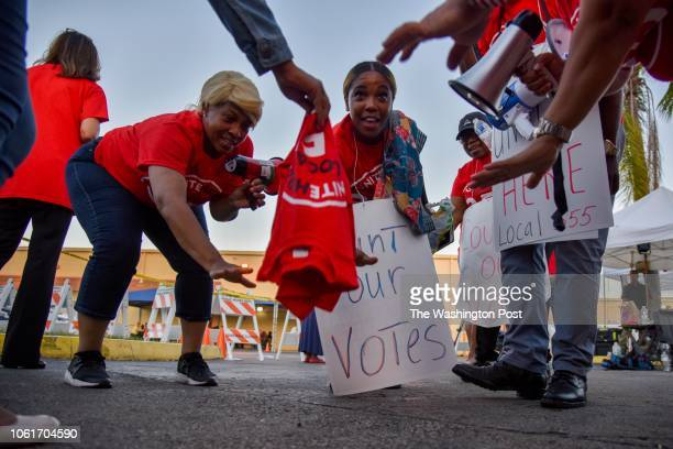 Demonstrators, including Rochelle Taylor, L center, and Rebecca Vedrine, R center, gather outside the Broward County Supervisor of Elections...