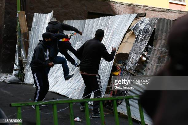 Demonstrators jump on a barricade during a protest on November 15 2019 in La Paz Bolivia Morales flew to Mexico alleging a coup under military...