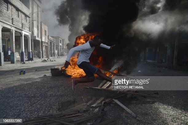 TOPSHOT A demonstrators jumps over a barricade during a protest demanding accountability from politicians for allegedly squandering billions of...