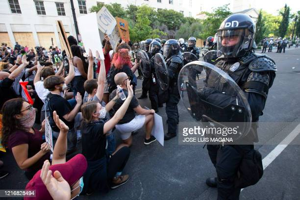 Demonstrators knee as police officers in riot gear push back outside of the White House June 1 2020 in Washington DC during a protest over the death...