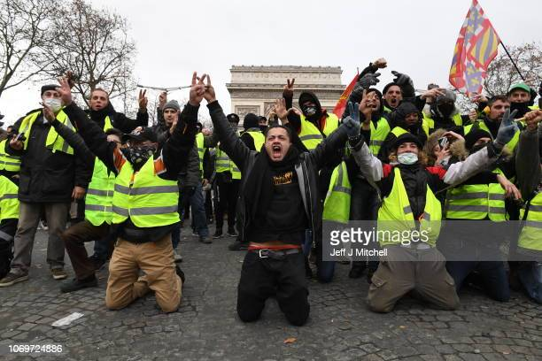Demonstrators kneel and gesture with victory signs as they take part in the demonstration of the yellow vests at the Arc de Triomphe on December 08...