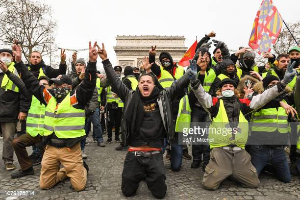 Demonstrators kneel and gesture with victory signs as they take part in the demonstration of the yellow vests near the Arc de Triomphe on December 8...