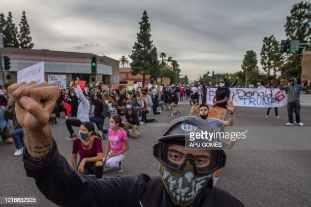 TOPSHOT Demonstrators kneel in an intersection while they march in Anaheim California on June 1 during a peaceful protest over the death of George...