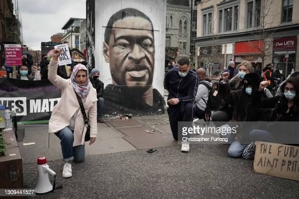 """Demonstrators kneel in front of a mural depicting George Floyd during a """"Kill the Bill"""" protest in Manchester City Centre on March 27, 2021 in..."""